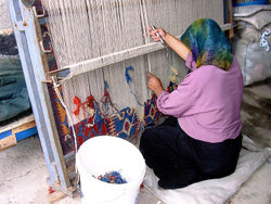 A Turkish woman in Konya works at a traditional loom. Vertical looms were probably the first to be invented.