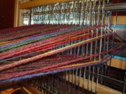 The yarn passes through the heddles in each shaft of this four-shaft table loom. This is a view from the rear of the loom.