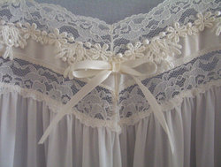Lace appliqué and bow at the bust-line of a soft nylon nightgown.