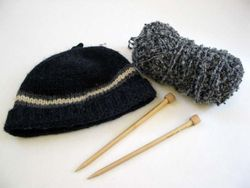 Knit hat, yarn, and knitting needles.