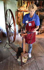 Spinning wheel demonstration in the Conner Prairie living history museum loom house, producing yarn from wool.
